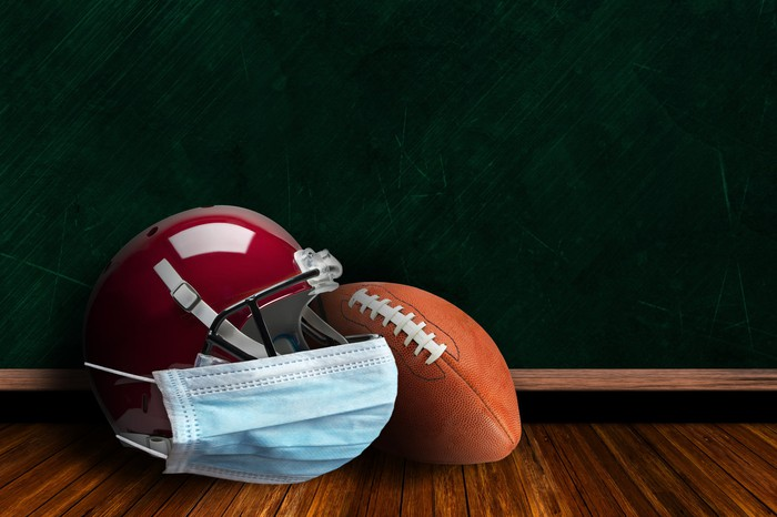 A football mask with a surgical face covering and a football.