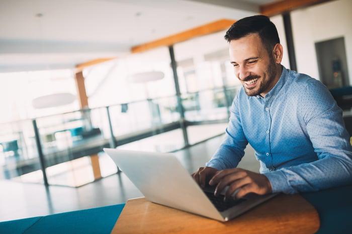 Man smiling while using laptop.
