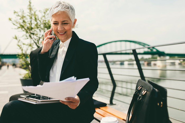 Smiling senior businesswoman sitting on bench and talking on cell phone