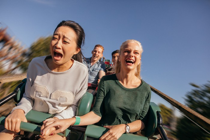 Two friends ride a roller coaster.