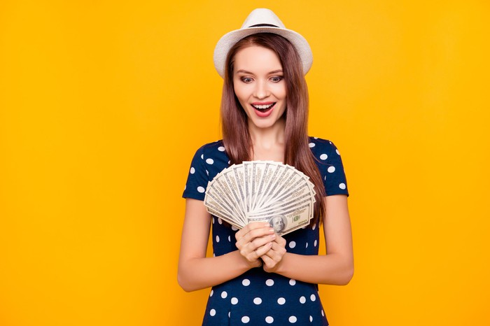 A person in a hat and polka dot dress smiles at a fanned handful of hundred-dollar bills.