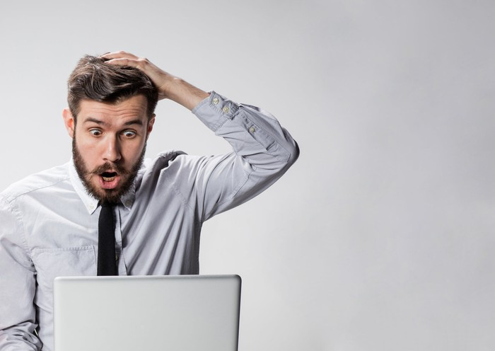 A surprised man places his hand on his head while looking at his computer screen.