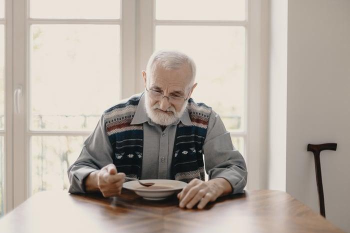 Older man at table eating soup