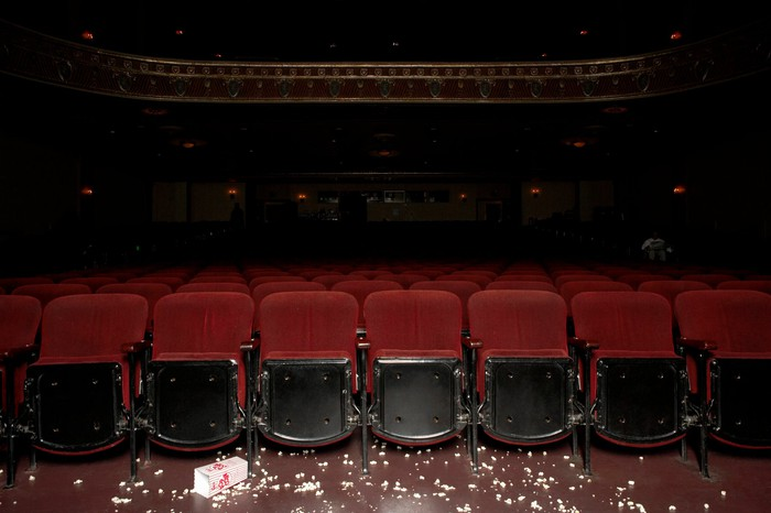 Darkened, empty movie theater with floor littered with popcorn.