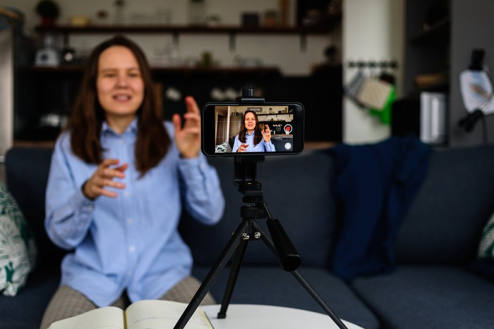 Woman recording a video with a smartphone placed on a tripod.