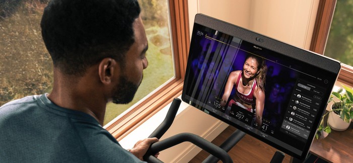 Man on stationary bike looking at fitness instructor on screen