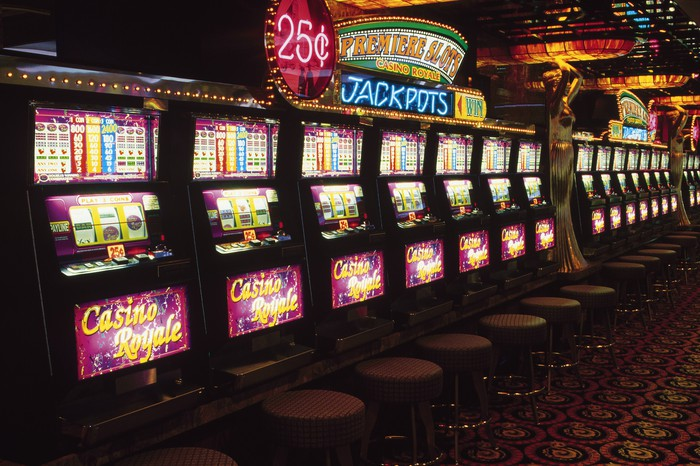 A casino with a row of slot machines and empty stools.