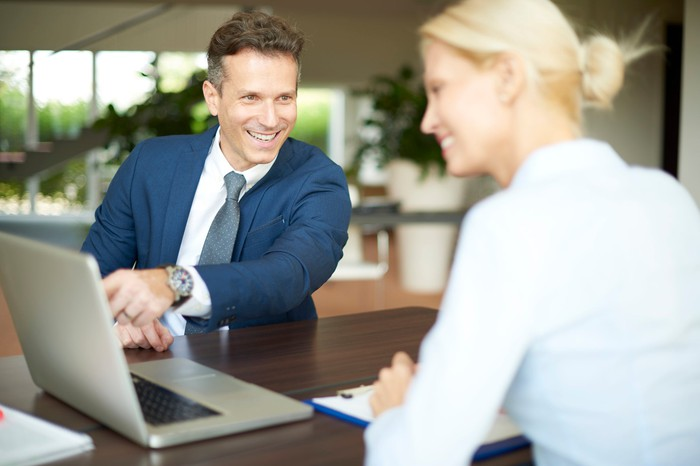 Cloud Computing: A man and a woman smile across the table while pointing at a shared laptop.