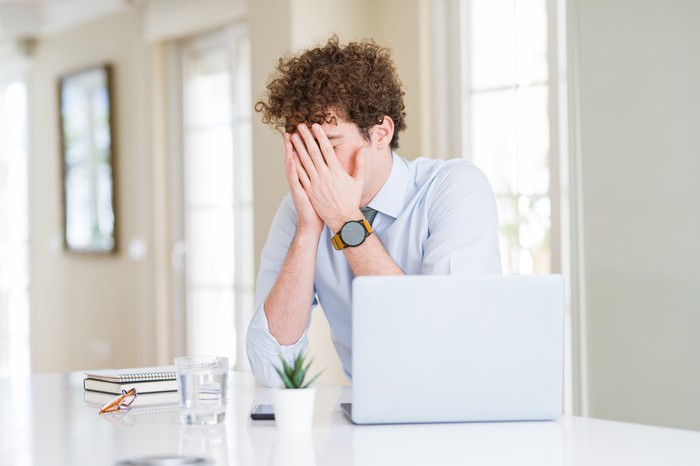 Man at laptop covering his face