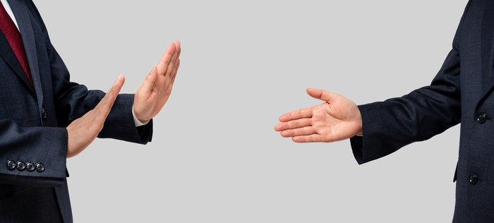 One businessman declines a handshake being offered by another businessman.