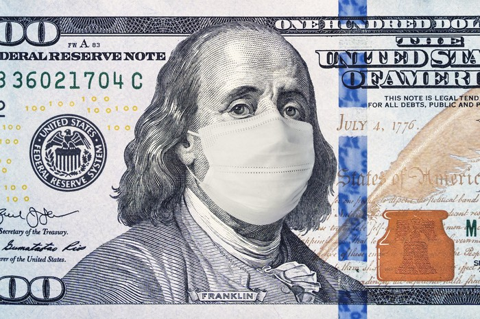 A $100 bill with a mask covering Benjamin franklin's face.
