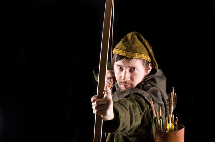 An archer in medieval clothing is aiming a bow and arrow at the viewer.