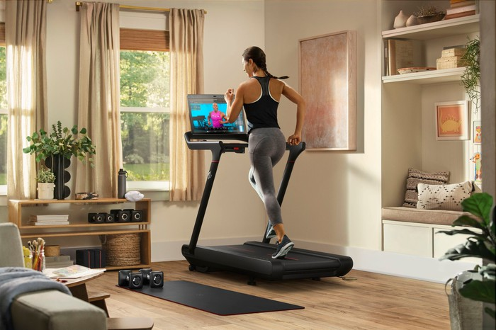 Woman running on Peloton's new Tread model in a furnished living room