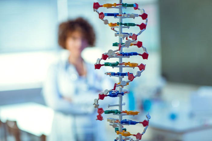 In the background, a medical professional looks at a DNA double helix model in the foreground.