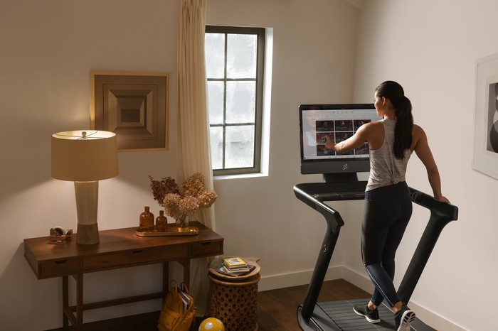 Woman exercising on a Tread+ next to a sideboard with a lamp on it