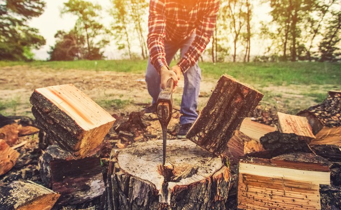 Lumberjack splitting a log in two with an axe