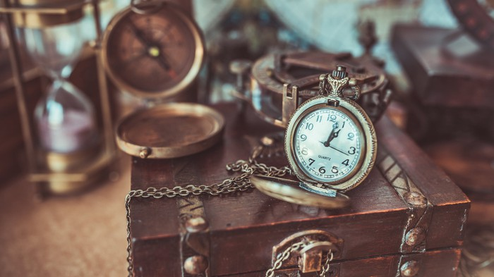 Antique items, including an hourglass, stopwatch, compass and moneybox, all stacked on a desk.
