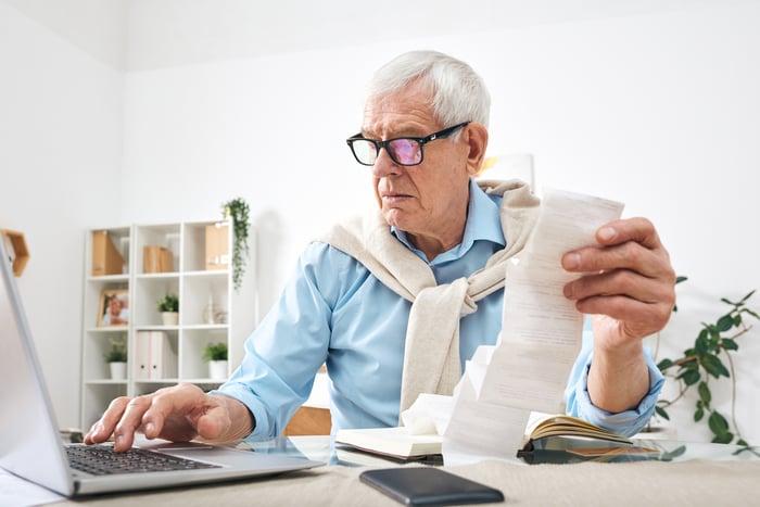 Older man at laptop holding receipt