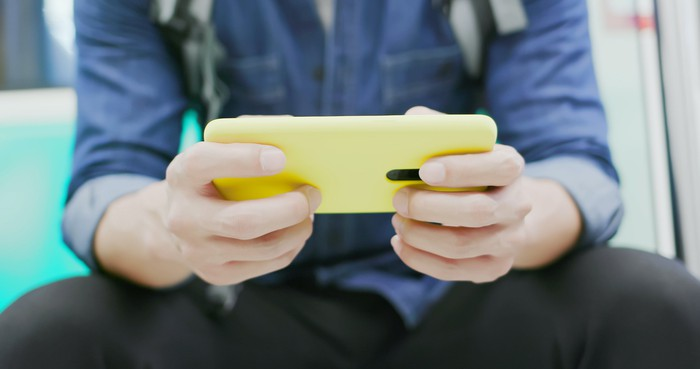 Person holding a smartphone horizontally and playing games on it