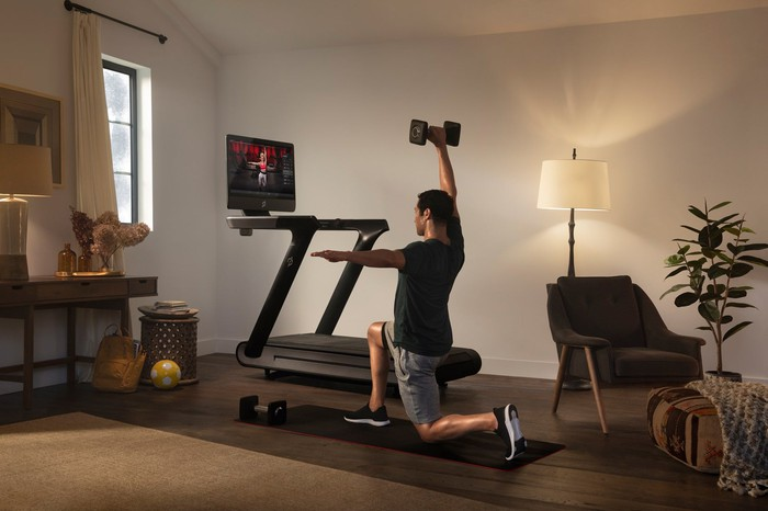 Person lifting weight in front of Peloton treadmill, with fitness instructor on screen.