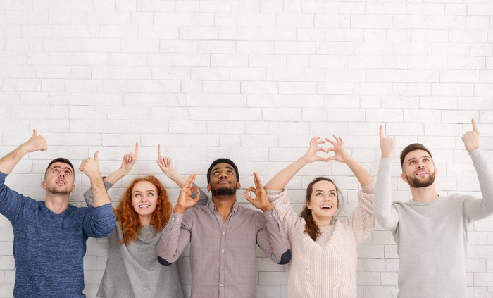 A group of young millennials look upwards against a white wall making hand gestures.