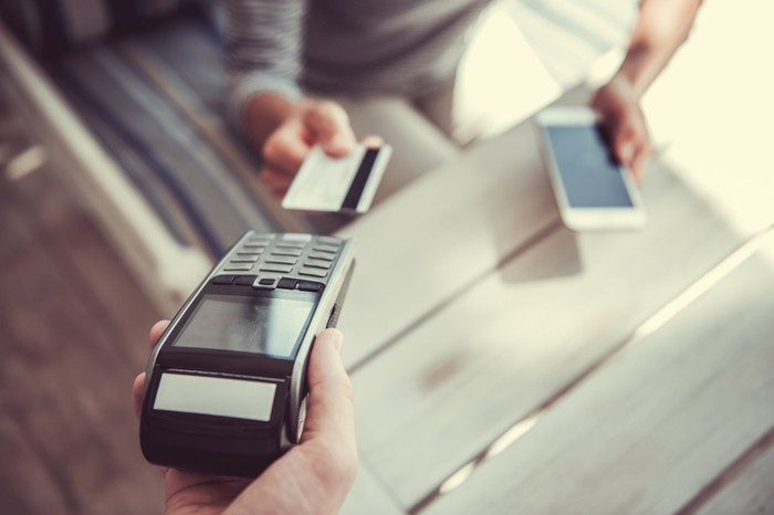 A payment being made with a credit card while the user holds a smartphone in the other hand.