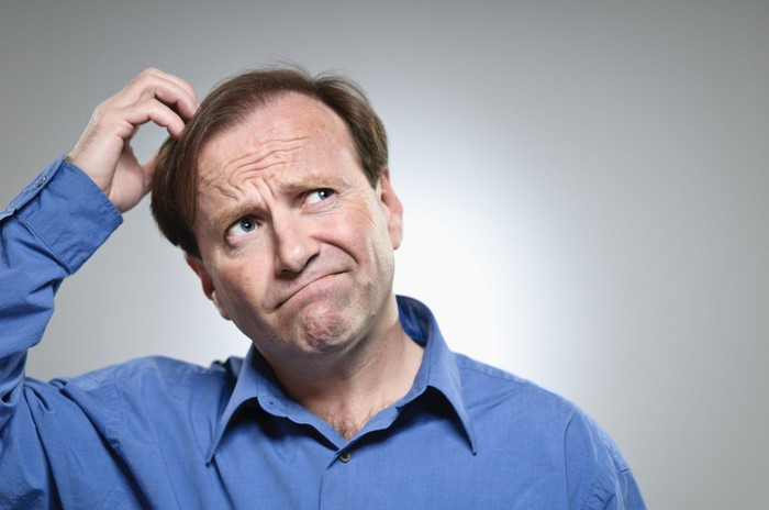 A visibly confused mature man scratching the top of his head.