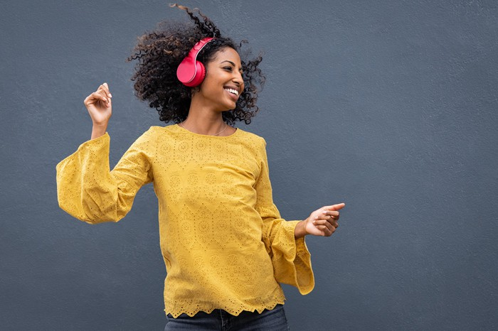 woman dancing and listening to music with headphones