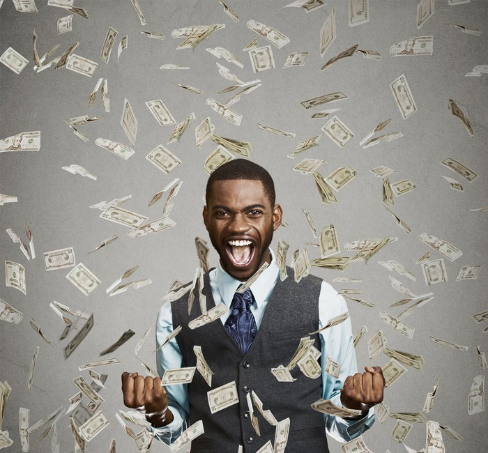 young man tossing money into the air and smiling for joy