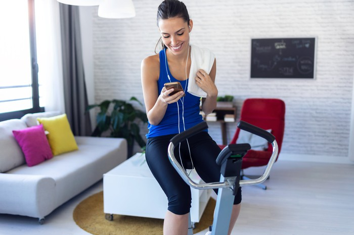 Lady sitting on exercise bicycle, smiling into her mobile phone with a towel around her left shoulder.
