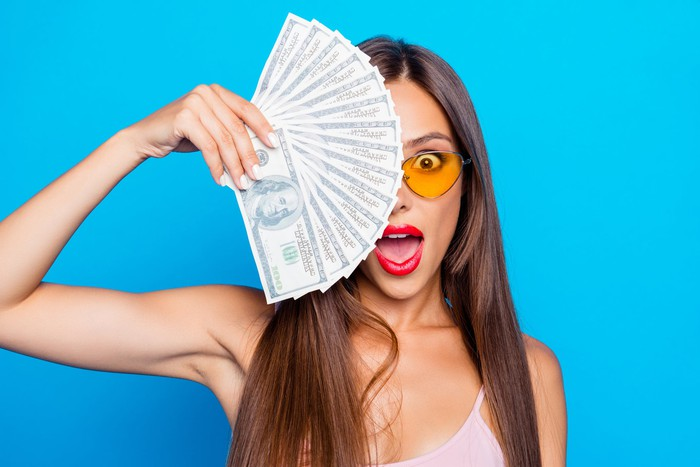 A woman holding a fanned out stack of hundred dollar bills while standing in front of a light blue background.