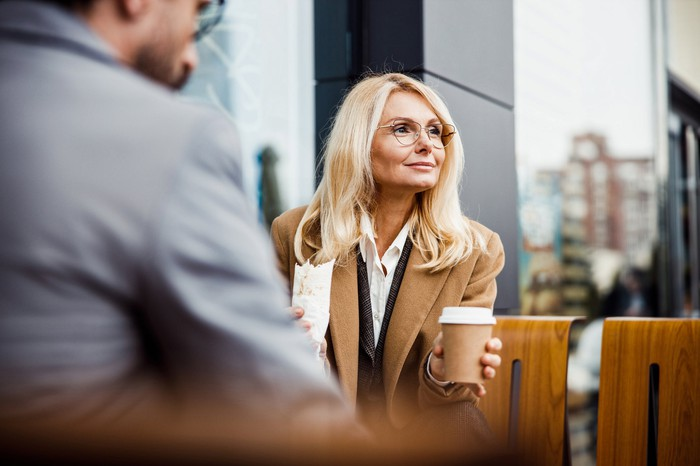 A businesswoman holds a cup of coffee in one hand and a burrito in the other.