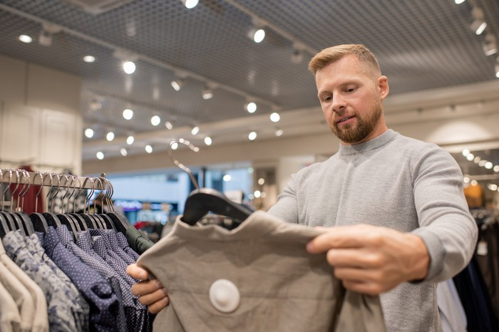 A young man holding a sweater in a retail store.