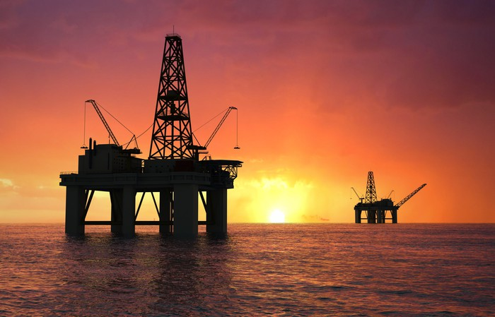Two offshore oil rigs at sunset.