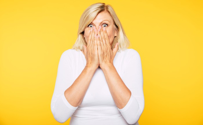 A surprised woman covers her mouth with her hands.