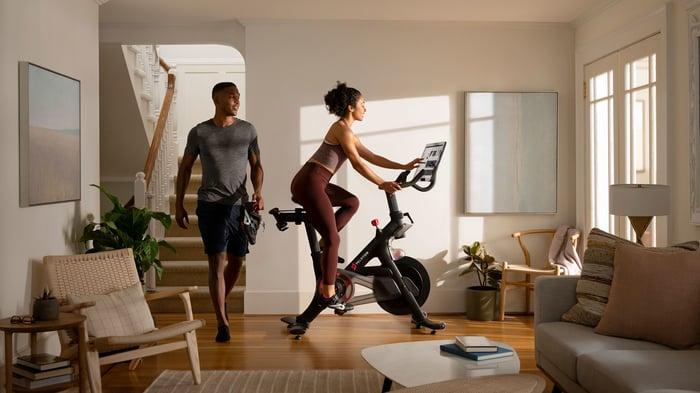 A couple sharing a workout on a Peloton bike.