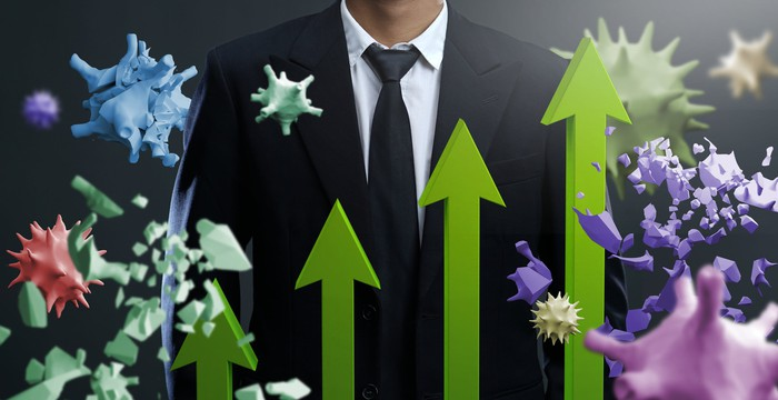 Businessman with green arrows pointing up and virus images