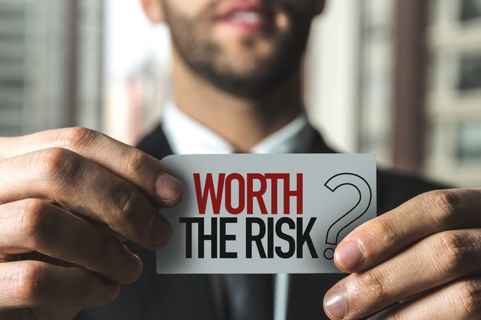 A young man in a suit holds up a sign that says worth the risk?