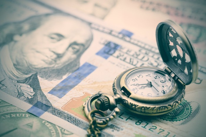 An antique pocket watch lying atop a messy pile of hundred-dollar bills.