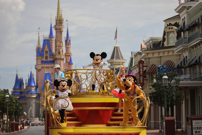 Mickey, Minnie, and Goofy are on a float in front of Cinderella's castle in the Magic Kingdom.