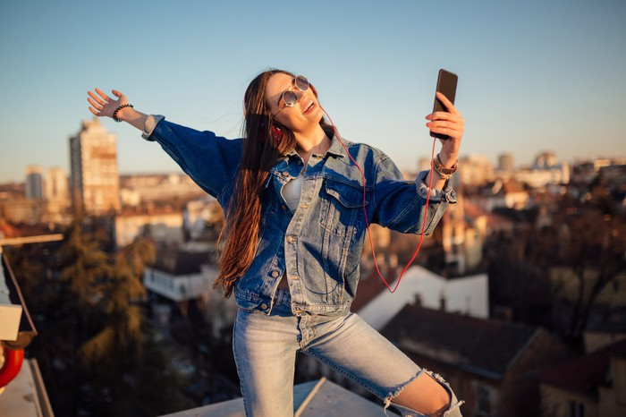 Woman dancing on rooftop with mobile phone