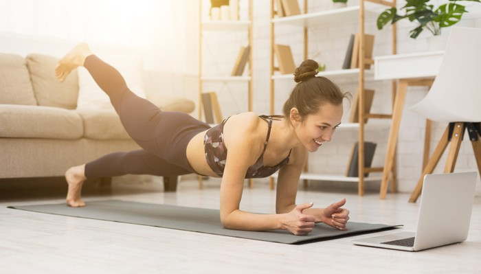 A woman does stretches at home in front of her laptop.