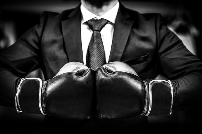 Person wearing black suit and boxing gloves.