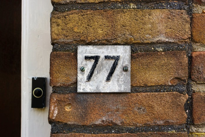 Number 77 on a brick wall