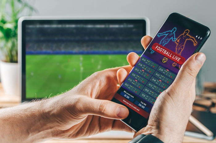 Person making mobile sports bet at home.
