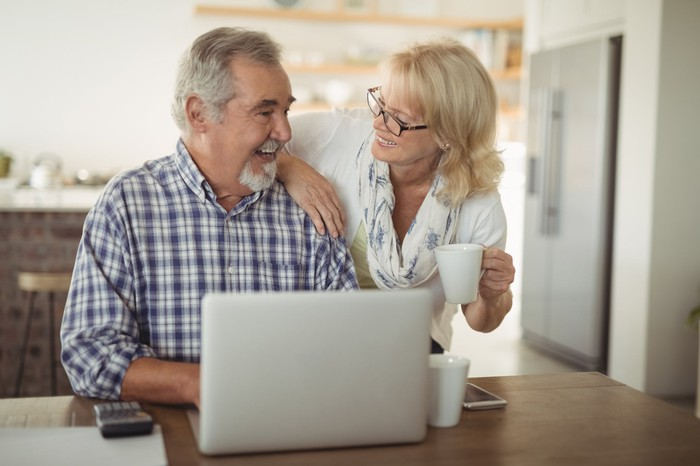 Older man typing on laptop with older woman leaning against his shoulder