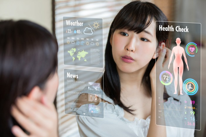 A woman looking at a computerized mirror displaying weather, news, and health information.