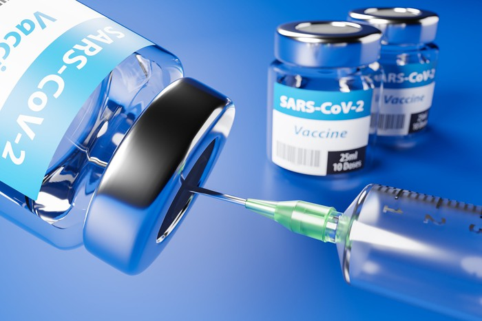 A syringe fills from a vial labeled as SARS-CoV2 Vaccine.