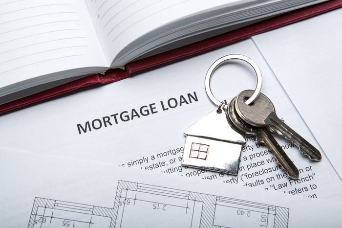 Mortgage loan papers with a set of house keys on top.