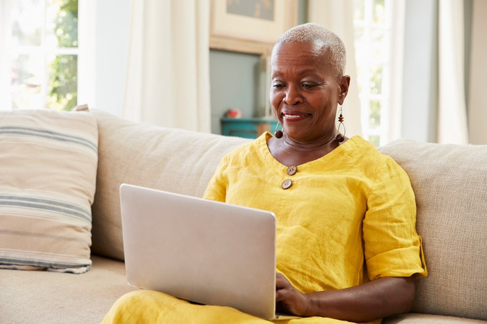 Smiling older woman sitting on couch with laptop in lap